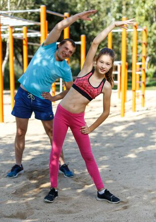 Smiling sporty tweenager girl doing exercises with her father in summer park