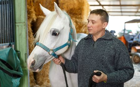 Portrait of man farm worker standing near white horse at stable