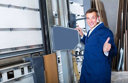 portrait of happy american man in uniform working on large automatic saw machinery indoors