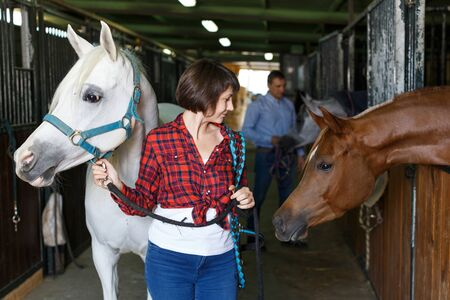 Portrait of young attractive woman who works at horse stable