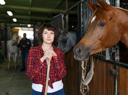 Portrait of woman farm worker standing at horse stable Фото со стока