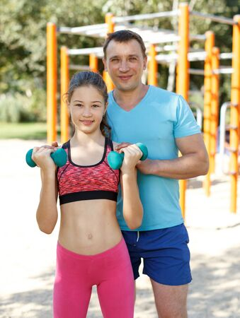Portrait of happy sporty family of father and preteen girl during training outdoors Фото со стока
