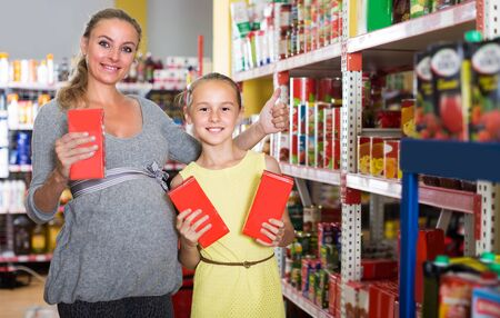 Mother with teenage girl are demonstrating their choise in food department in supermarket.