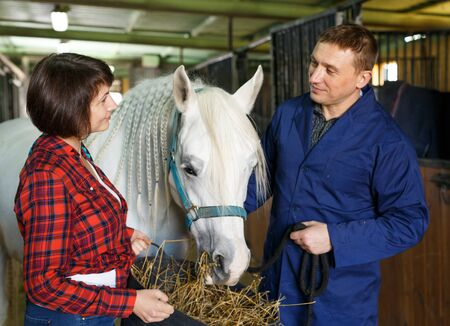 Female and male farm workers feeding roan horse with hay at stable Фото со стока