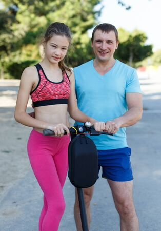 Athletic man teaching his tweenager daughter to ride kick scooter outdoors