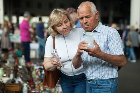 Portrait of positive adult family looking for vintage goods at flea market