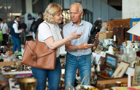 Elderly couple in flea market chooses antique items