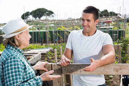 Elderly woman and young man talking on the border of the garden plot Stock Photo