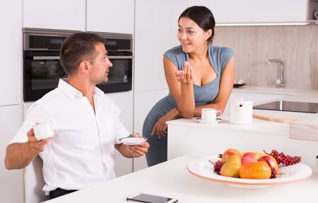 Happy young couple spending time together, drinking tea in stylish home kitchen Stock fotó