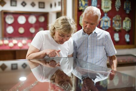 Senior couple looking at stands with exhibits in historical museum hall