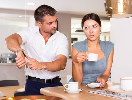 Annoyed man insisting that his girlfriend drink tea faster, pointing at clock