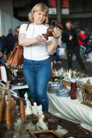 Mature woman buys handmade ceramic vase at flea market