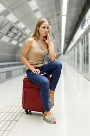 Young tired woman waiting subway train sitting on red suitcase