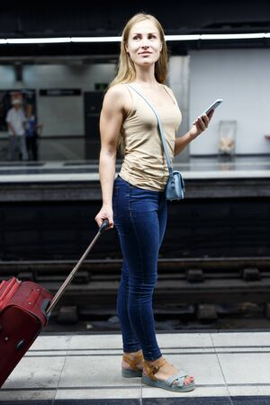 Portrait of young woman traveler with red suitcase walking in modern metro and using smartphone Фото со стока