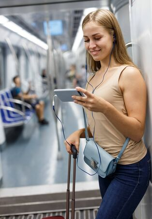Young woman traveling on underground and listening music with headphones Imagens