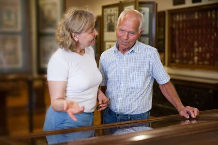 Senior couple looking at stands with exhibits in historical museum hall Banque d'images