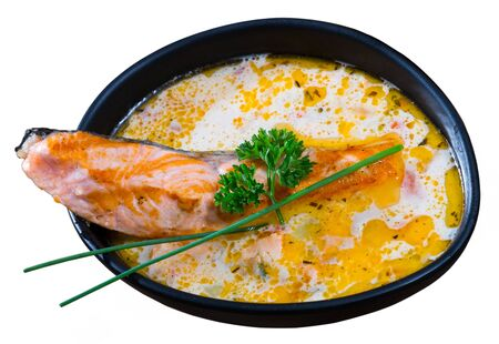 Bowl of creamy soup with salmon, cheese and vegetables garnished with fresh greens. Isolated over white background Stockfoto