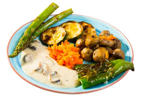 Healthy meal - baked mushrooms, zucchini, asparagus, bell pepper, carrots with vegan sauce. Isolated over white background