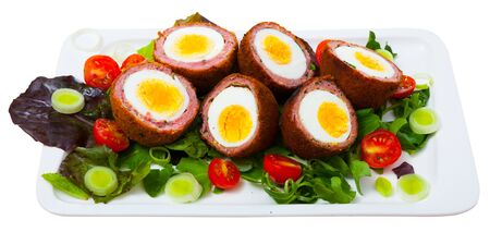 Dish of traditional Scottish cuisine of scotch eggs served with greens, leek and tomatoes at plate. Isolated over white background