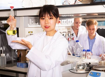 Intelligent Chinese female student performing experiments in university laboratory, holding test tube with chemicals