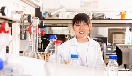Portrait of diligent  positive Asian female scientist registering results of research in notebook at biochemical laboratory