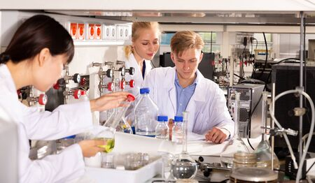 Focused student of Faculty of Chemistry with his female coursemates performing experiments in university laboratory, recording results in workbook