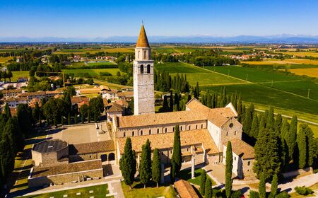 Aerial view of summer landscape of Aquileia township overlooking Basilica di Santa Maria Assunta with Gothic bell tower, Italy