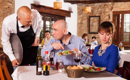 Upset couple complaining to waiter about quality of food in restaurant