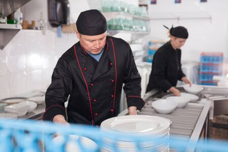 Confident kitchen worker arranging cleaned dishes, preparing for serving