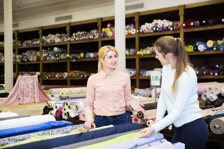 Young saleswoman of tissue store consulting female buyer about new trendy fabrics for dressmaking 免版税图像