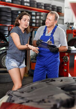 Young woman client expressing dissatisfaction to mechanic with results of her car repair in the auto workshop 写真素材
