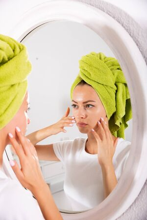 Young female in towel looking at her clear skin in mirror at home