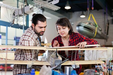 Positive glad pleasant  couple enjoying their hobbies - modeling light airplanes in aircraft hangar