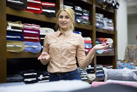 Young female seller of fabric shop showing new trendy textiles of high quality for dressmaking