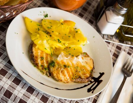 Codfish fillet with green sauce and potato served on plate