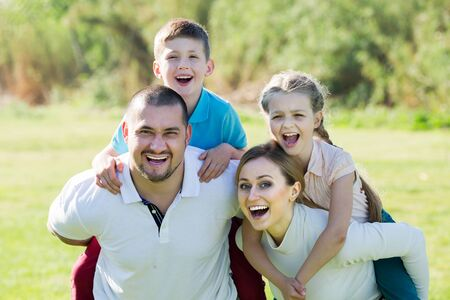 Smiling parents holding two kids on the shoulders outdoors