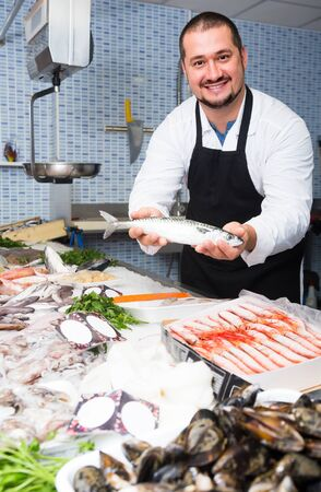 Positive seller in black apron showing fish in hands