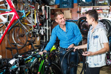 Father 40s and his son teenager choosing new wheel lid for bicycle in sport hypermarket