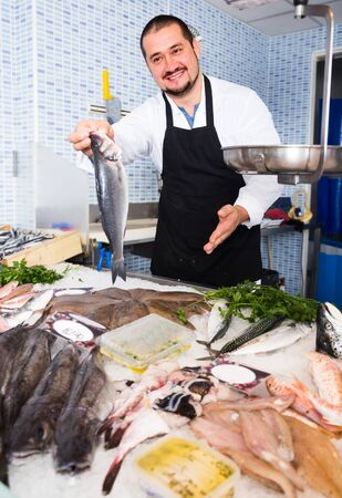 Man in black apron and white cover-slut behind counter holding row fish Stock Photo