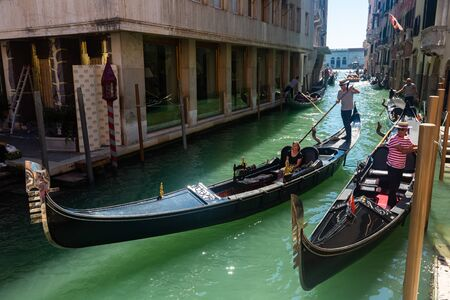 VENICE, ITALY - SEPTEMBER 05, 2019: Picturesque view of canals in romantic Italian city of Venice with gondoliers carrying tourists on gondolas on sunny autumn day