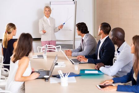 Business woman presenting strategy to colleagues in modern office Imagens