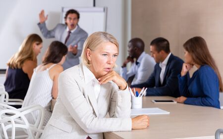 Portrait of frustrated mature woman sitting in office on background with angry boss scolding subordinates