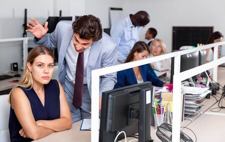 Outraged angry  upset  manager expressing dissatisfaction with work of frustrated young woman in modern office Stock Photo