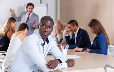 Frustrated young African businessman sitting at desk in meeting room on background with colleagues scolded by angry boss