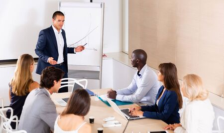 Businessman making presentation on staff meeting at office