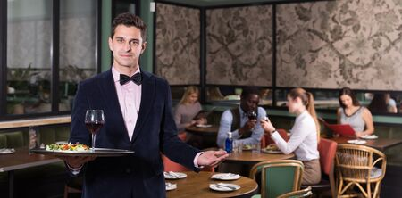 Portrait of smiling waiter with serving tray meeting restaurant guests