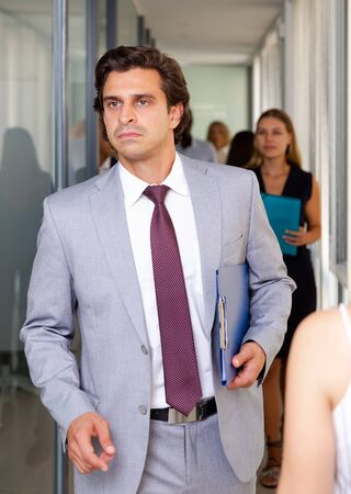 Portrait of successful businessman in formal suit walking through office