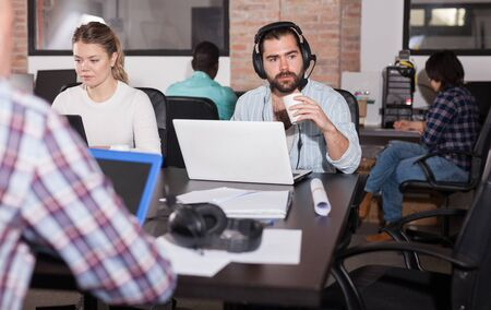 Focused bearded freelancer wearing headset discussing new project with his partner online in open plan office