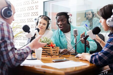 Irritated African male and European female radio presenters emotionally talking with guests in sound broadcasting station. Focus on man