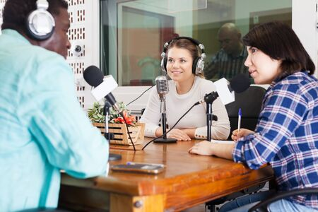 Positive international team of radio hosts interviewing guest in sound broadcasting station Archivio Fotografico